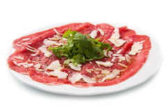Carpaccio of beef on arugula. White dish with carpaccio of beef on arugula over white background royalty free stock images