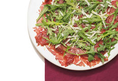 Carpaccio of beef with rucola and Parmesan on red napkin,  Royalty Free Stock Images