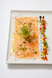 Carpaccio di color salmone su un piatto bianco Carpaccio dei frutti di mare - Salmon Carpaccio Immagine Stock