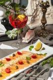 Carpaccio dos salmões com tomates de cereja e vinho e Aperol Foto de Stock