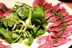 Carpaccio mit Rocket-Salat Stockfotografie