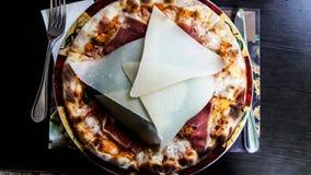 Carpaccio pizza med parmesanskivor på restaurangen royaltyfria bilder