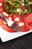 Carpaccio. On a plate with parmesan and pignolia stock photo