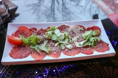 Carpaccio of red beef and pork with tomatoes sprinkled with cheese and greens on a white rectangular plate on a table in a caf. E, restaurant Stock Photography