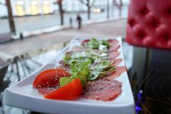 Carpaccio of red beef and pork with tomatoes sprinkled with cheese and greens on a white rectangular plate on a table in a cafe. Restaurant Royalty Free Stock Photography