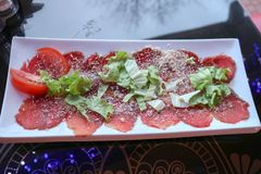 Carpaccio of red beef and pork with tomatoes sprinkled with cheese and greens on a white rectangular plate on a table in a cafe. Restaurant Stock Photography
