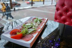 Carpaccio of red beef and pork with tomatoes sprinkled with cheese and greens on a white rectangular plate on a table in a cafe. Restaurant Stock Image