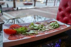 Carpaccio of red beef and pork with tomatoes sprinkled with cheese and greens on a white rectangular plate on a table in a cafe. Restaurant Stock Photos