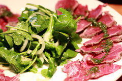 Carpaccio with Rocket Salad. Beef Carpaccio with Rocket and onion salad Stock Photography