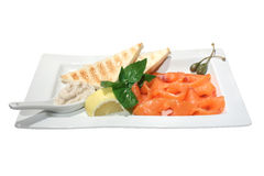 Carpaccio of salmon. Italian dish: carpaccio of salmon with horseradish sauce, lemon, basil, toasts and capers. Isolated on white Stock Photography