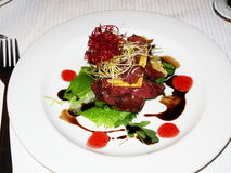 Carpaccio tower. Starter of impala and ostrich carpaccio nicely decorated with balsamic dressing, parmesan shavings and beetroot sprouts stock images