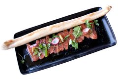 Carpaccio of tuna with a baguette. On a white background Royalty Free Stock Image