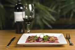 Carpaccio und Rotwein Stockbild