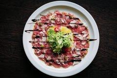 Carpaccio van kalfsvlees in een witte plaat Stock Afbeelding
