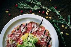 Carpaccio van kalfsvlees in een witte plaat Stock Afbeeldingen