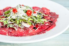 Carpaccio wołowina z ruccola, parmesan serem i wysuszonym pomidorem, obraz royalty free