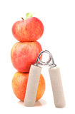 Carpal expander and a stack of three red apples Royalty Free Stock Photos