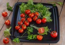 Carpal rojo del puño de los tomates en un disco negro con las puntillas del perejil y de la ensalada verdes Foto de archivo libre de regalías