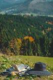 Carpathian alpint berg Sidor av en öppen bok, en hatt och en thermo kopp majestätisk liggande Natur- och utbildningsbegrepp royaltyfri bild