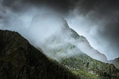 Mysterious mountain look with foggy weather and dark stormy sky. stock photos