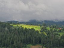 Carpathian fog. Landscape, background, view, land, mountain, house, tree, trees, wood, clouds, sky, nature, morning, sunlight village Royalty Free Stock Images