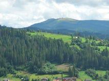 Carpathian landscape. Landscape, background, land, view, mountain, trees, grass, house, wood, sunlight, clouds, sky Stock Photos