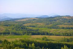 Carpathian mountain landscape. A panoramic view overlooking rolling fields and  hills with the Carpathian mountains of Romania in the distance Royalty Free Stock Photography
