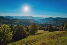 Carpathian Mountains. The autumn sun with rays, mountains and hills Stock Photos