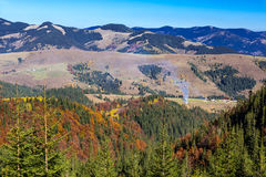 Carpathian Mountains Autumnal Panorama. Fir Pine Forest with some Aspen and Birches Bright Autumnal Colors Local Village Making Column of Smoke royalty free stock photos