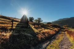 Carpathian Mountains. Dawn of the sun, the road to the village, haystack Royalty Free Stock Photography