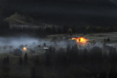 Carpathian Mountains. Moonlit Night in the mountains, the village on the hill in the fog. Royalty Free Stock Photo