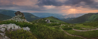 Carpathian Mountains. Panorama. The rays of the rising sun illuminate the village in the valley Stock Photo