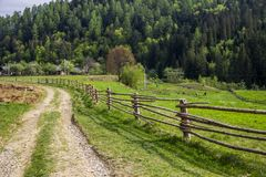 Carpathian rural landscape. A rural landscape at carpathian mountains with fence, home and some cows at back, national park Skolevski beskidy, Lviv region of Stock Images