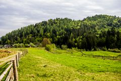 Carpathian rural landscape. A rural landscape at carpathian mountains with fence, home and some cows at back, national park Skolevski beskidy, Lviv region of Stock Image