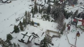 Carpathian ski resort from a height. Flight over ski lifts. Bird`s eye view of people descending on skis and snowboards. stock video