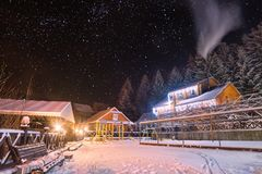 Carpathian village covered with snow. Ukrainian carpathian village covered with snow. Yard illuminated by christmas lights. Many stars in a night sky Royalty Free Stock Photos