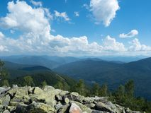 Carpathians mountains, west Ukraine. Pile of grey natural stones. White clouds flowing in blue sky. Mountain ranges with. Green woods. Ukrainian nature royalty free stock image