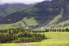 carpathians Paisagem da montanha Vila no vale entre florestas coníferas Foto de Stock Royalty Free