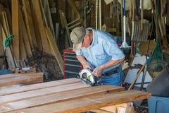 CarpCarpenter sawing 2x8 planks for garden boxes for veterans. Royalty Free Stock Photos