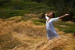 Carpe Deim. A beautiful Hawaiian woman stands in a meadow surrrounded by wind-blown grass, dressed in white with hands and face raised to the sky Stock Photo