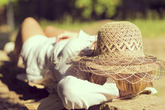Carpe diem. Young girl lying on a brick wall in a park on a sunny summer day, wearing a hat Stock Photos