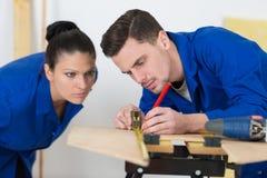 Carpentary studenter som utbildar på seminariet som mäter woodboard Royaltyfria Foton
