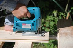 Carpenter. With fretsaw at outdoor work Stock Photos