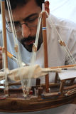 The Carpenter. A workman finishes the final touches on an Arabian wooden dhow model royalty free stock images