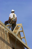 Carpenter. On the roof of a house being built wearing safety harness Royalty Free Stock Photo