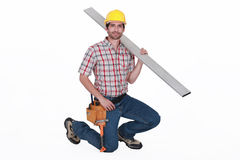 Carpenter against  carrying steel post Stock Image