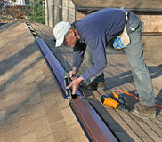 Carpenter applying caulk to ridge vent stock photos