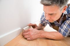 Carpenter applying skirting on wall Royalty Free Stock Photography