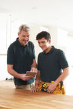 Carpenter And Apprentice With Digital Tablet Fitting Luxury Kitc Stock Photo