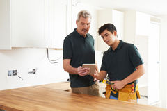 Carpenter And Apprentice With Digital Tablet Fitting Luxury Kitc Stock Photos